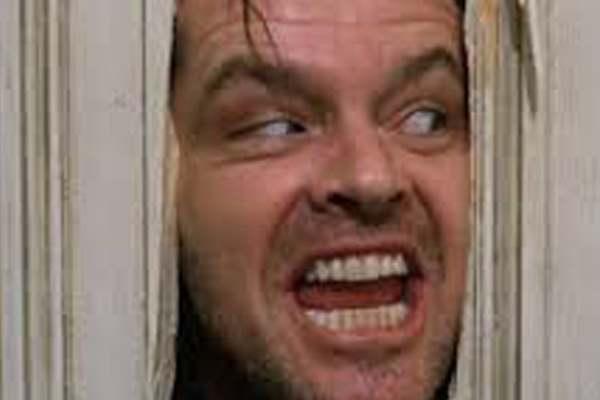 Imagen mítica de El Resplandor. Jack Nicholson mirando a través de la puerta rota.